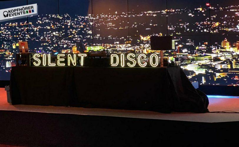 DJ Pult mit Silent Disco Schriftzug und der Skyline von Stuttgart im Hintergrund