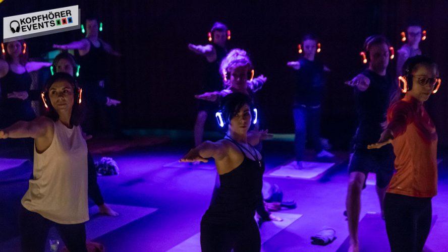Gruppe von Menschen beim Silent Disco Yoga mit Kopfhörern